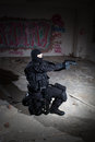 Anti terrorist unit policeman during the night mission soldier operation in criminal s house aiming at target very harsh lighting Royalty Free Stock Photo