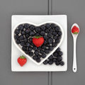 Antioxidant superfood blueberry and strawberry fruit in a heart shaped dish on a square plate with porcelain spoon Royalty Free Stock Photos