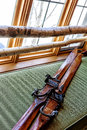 Antiquated skis pair of leaning on a green sofa with focus on the boot blocking mechanism Royalty Free Stock Photo