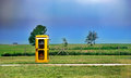 Antiquated yellow phone box is standing lonely in the nature Stock Image