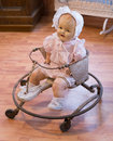 Antique baby walker a very old with vintage doll in it Royalty Free Stock Photo
