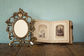 Antique blank victorian style frame and old open photograph album with vintage necklace on wooden table retro filtered image Royalty Free Stock Photography