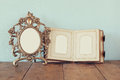 Antique blank victorian style frame and old open photograph album on wooden table. retro filtered image Royalty Free Stock Photo