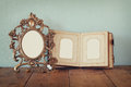 Antique blank victorian style frame and old open photograph album on wooden table. retro filtered image. Royalty Free Stock Photo