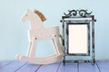 Antique blank vintage style frame and old rocking horse over woo Royalty Free Stock Photo