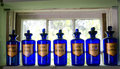 Antique blue apothecary bottles sit on a window sill Stock Image