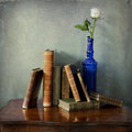 Antique books and a pink rose in a blue bottle interior still life vintage composition of on wooden table single glass decorated Royalty Free Stock Photography