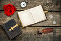 Antique books writing accessories and red rose flower over rustic wooden background vintage keys pocket watch glasses feather Royalty Free Stock Image