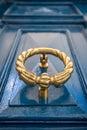 Antique brass door knocker on blue door.
