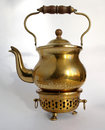 Antique brass teapot old fashioned on stand with shadows Stock Images