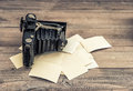 Antique camera and old photos on wooden background Royalty Free Stock Photo