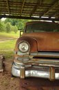 Antique car rusting away in an old barn Stock Photo