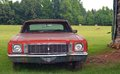 Antique car sitting in a field rusting away Royalty Free Stock Images