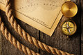 Antique compass and rope over old map Royalty Free Stock Photo