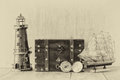 Antique compass, vintage lighthouse, wooden boat and old chest on wooden table. black and white style old photo Royalty Free Stock Photo
