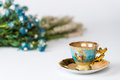 Antique cup and saucer decorated in gold blue with blurry background of french flowers Royalty Free Stock Photography