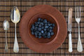 Antique cutlery and jarrah bowl filled with berries a photograph of some silver a wooden blueberries is a large sized hardwood Royalty Free Stock Image