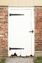 Antique door an old white with black iron hinges is surrounded by bricks Royalty Free Stock Photography