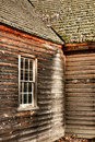 Antique farmhouse old window and clapboard siding historic farm building with wood sash exposed outside walls under an wooden Stock Photography
