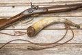 Antique firearm powder horn wood background