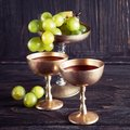 Antique golden goblets with red wine and bunch of grapes Royalty Free Stock Photo