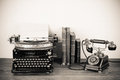 Antique phone and typewriter a still life with an a on a table with old books Royalty Free Stock Photo