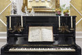 Antique piano with candles and musical score. Indoor decoration. Royalty Free Stock Photo