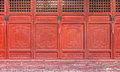 The antique red Chinese wooden carved doors of temple