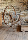 Antique spinning wheel in stone mill Royalty Free Stock Image