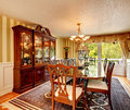Antique style dining room bright with table set carved wood cabinet with glass doors hardwood floor and rug Stock Images