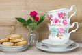 Antique teacups and cookies red roses on a wooden background Stock Photos