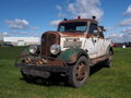 Antique tow truck parked in a grassy field Royalty Free Stock Photo