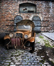Antique truck on back alley road a golden with cargo parked a cobble stone in front of an old brick building Royalty Free Stock Images