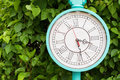Antique turquoise color clock in the garden Royalty Free Stock Photo