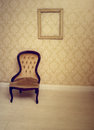 Antique upholstered chair in a wallpapered room with an empty vintage wooden picture frame hanging on the wall suitable as an Royalty Free Stock Photography
