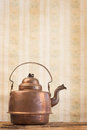 Antique vintage copper kettle on the background of old wallpaper Royalty Free Stock Photo