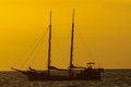 Antique vintage sail vessel on the ocean at sunset Stock Image