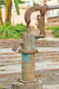 Antique water pump iron next to iron trough beside red brick sidewalk and green grass Royalty Free Stock Photography