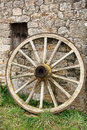 Antique wood wagon wheel against old stone wall and weathered cart with vintage wooden spokes leaning an farm building Royalty Free Stock Images