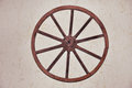 Antique wooden cartwheel on a background of white adobe wall Royalty Free Stock Photos