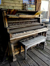 Antique wooden piano a in ruins sits on a platform the keys and finish are weathered Stock Images