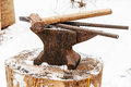 Anvil with blacksmith tongs hammer in smithy Royalty Free Stock Photography