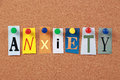Anxiety single word the in cut out magazine letters pinned to a corkboard Royalty Free Stock Photography