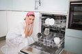 Anxious charming woman sitting next to dish washer in bright kitchen Royalty Free Stock Photos