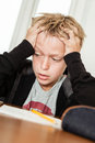 Anxious child struggling to complete homework single blond boy in black sweater holding his head in frustration and desperation as Stock Photo
