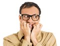 Anxious man closeup portrait of a nerdy guy with big glasses biting his finger nails craving something scared looking side Stock Image