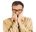 Anxious man closeup portrait of a nerdy guy with big glasses biting his finger nails craving something scared looking at you Royalty Free Stock Photography