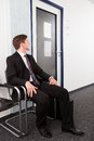 Anxious man sitting on chair waiting for job interview Royalty Free Stock Images