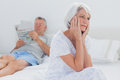 Anxious mature woman sitting on bed women while husband is reading a newspaper the background Stock Image