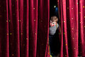 Anxious young actor looking out from the curtains boy in his costume and makeup on stage to check that everything is going to Royalty Free Stock Photography